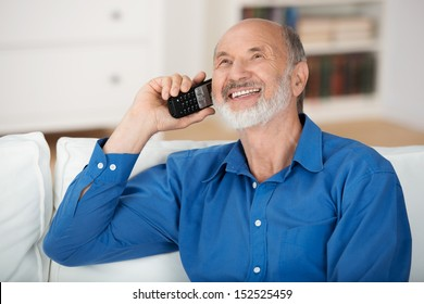 Delighted senior man chatting on a mobile phone while relaxing on a sofa in his living room, natural close up portrait