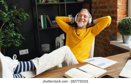 Delighted senior man in trendy clothes holding hands behind head and listening to music in headphones while resting in home office