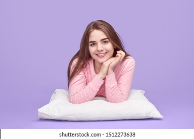 Delighted teenager in pink nightwear clasping hands and smiling for camera while lying on soft pillow and dreaming against violet background
