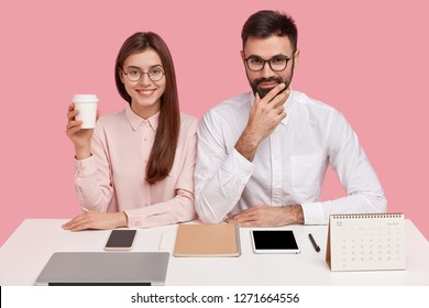 Delighted woman has toothy smile, wears optical glasses, holds takeaway coffee, has pleased expression, unshaven guy in white shirt, sit at office desk with neatly arranged things. Perfectionism