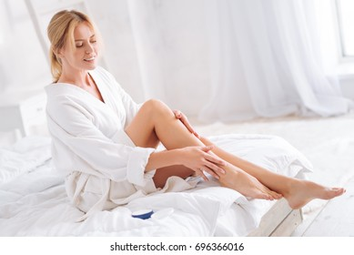 Delighted woman massaging her legs