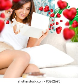 Delighted woman reading a greeting card sitting on the sofa at home. Beautiful red hearts are floating around her