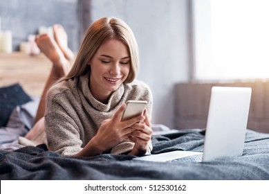 Delighted woman using smartphone and laptop in bed