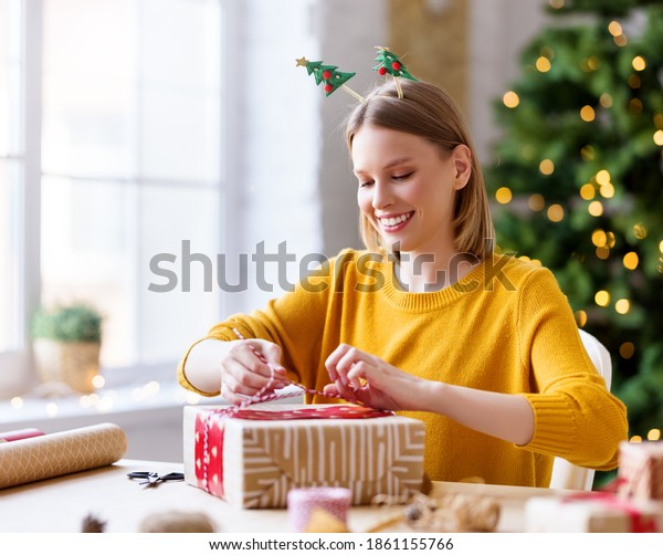 Delighted young female smiling and wrapping decorative paper around present box while sitting at table and preparing for Christmas celebration at home