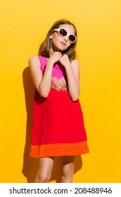 Delighted young girl holding hands on chest and looking away. Three quarter length studio shot on yellow background.