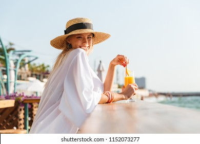 Delighted young girl in summer hat and swimwear resting at the sunny beach, sitting at a cafe with a cocktail