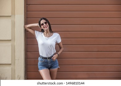 Delighted young modern woman in denim shorts and top with sunglasses having rest by wooden wall in summer
