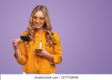 Delighted young woman in casual outfit and trendy sunglasses entering credit card credentials into smartphone while paying for online purchases against violet background
