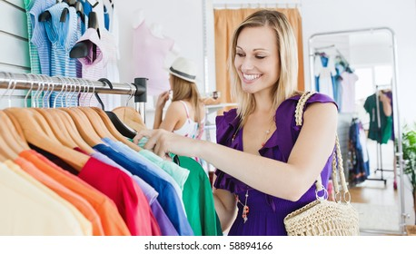Delighted young woman choosing clothes in a clothes store