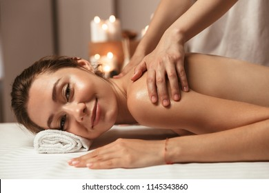 Delighted young woman having massage in the spa salon