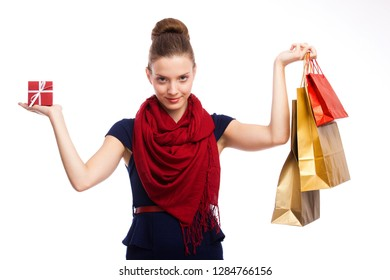 Delighted young woman holding shopping bags and gift box - looks very happy
