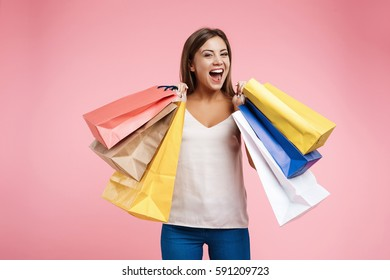 Delighted young woman holding shopping bags and looks very happy