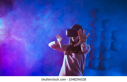 A delighted young woman in virtual reality glasses, against the background of a futuristic pattern on the wall in the shape of a pixel heart, get experience in virtual space.