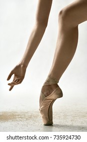 Delightful ballerina is posing in the studio on the light background. She stands on the toe and holds the arm next to the leg. Girl wears beige pointe shoes. Closeup. Vertical.