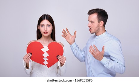A delightful brown-haired woman with blue eyes and a white knitted sweater sad holds in her hands two halves of a broken heart, a young guy in a blue shirt stands next to him and yells at her.