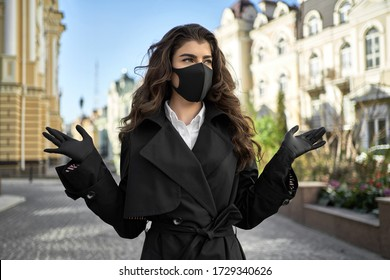 Delightful brunette woman in a black protective mask with latex gloves stands on empty sunny city street during COVID-19 quarantine. She wears a black trench coat with a white shirt. Horizontal.