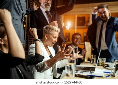 Delightful business people enthusiastically exulting in bright office, young woman happily raising hands smiling broadly at meeting