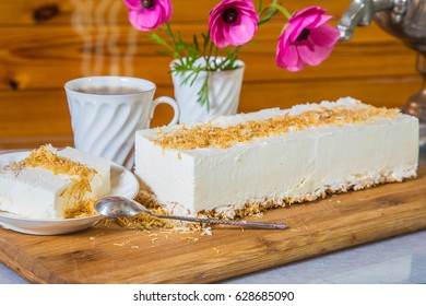 Delightful cheesecake with crumbled kadaif. Professional bakery. On a saucer with a spoon lies a piece of cake. The background is cup with tea and vase with flowers