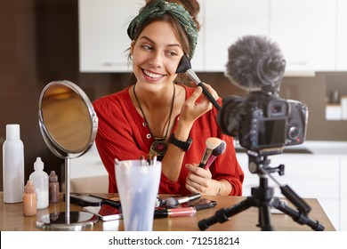 Delightful female model applying make up with cosmetic brush, looking at camera mounted on tripod, advertising new cosmetics for fashion journal or magazine. Successful female earning money online