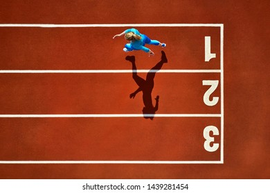 Delightful girl in a blue sportswear and sneakers starts her sprint run with a long jump on the running track number 1 at the stadium outdoors. Sun shines onto her body. Top view aerial photo.
