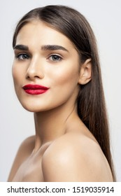 A delightful lady with dark hair and bright makeup naked shoulders red lips a beautiful face