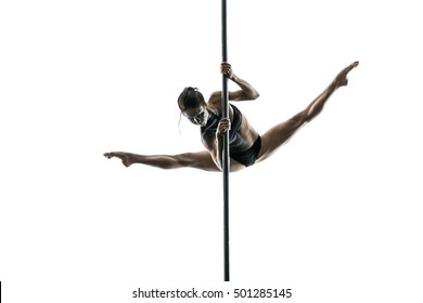 Delightful pole dancer with a body-art makes a split while hangs on a pylon in a studio on a white background. She holds her hands on the pylon. Girl wears black sport underwear. Horizontal.
