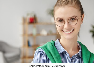 Delightful pretty woman in round glasses, wears shirt, stands indoors, smiles happily, demonsrtrates white perfect teeth. Happy talented female student rejoices finishing work on course paper