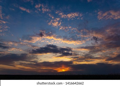 Delightful sunsets in the steppe. At sunset, the sun breaks through the clouds and clouds with unusual light, it is orange, then yellow, then red, then purple, and sometimes even bloody.