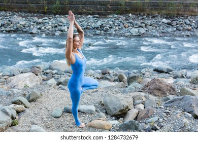 Delightful young blond female in blue dress suit stands in Vrikshasana pose with her eyes closed and enjoys the sounds of nature while standing by mountain stream on warm summer day. Unity with nature