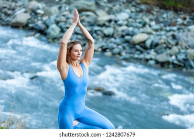 Delightful young blond woman in blue dress suit stands in Vrikshasana pose with her eyes closed and enjoys the sounds of nature while standing by mountain stream on warm summer day. Unity with nature