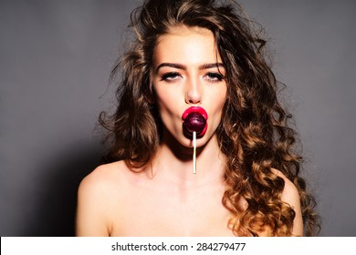 Delightsome young undressed woman with curly hair and bright pink lips holding purple round lollipop in mouth looking forward standing on grey background, horizontal picture