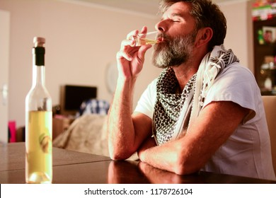 Delirium tremens. Alcoholism, alcohol addiction and people concept. A man with a seventh beard feels relieved after drinking alcoholic drinks at the table in the living room.