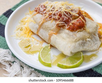 A delishious Mexican burrito with salsa, cheese, hot sauce and lime.