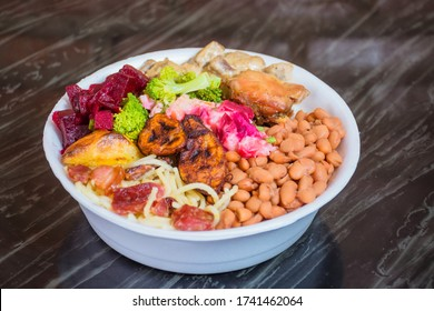 Deliver food, marmita ou marmitex with rice, beans, beets, broccoli, mayonnaise with vegetables, fried chicken, beef stroganoff, pasta and bacon on a dark marble table.