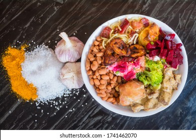 Deliver food, marmita ou marmitex with rice, beans, beets, broccoli, mayonnaise with vegetables, fried chicken, beef stroganoff, pasta and bacon on a dark marble table. Top view.