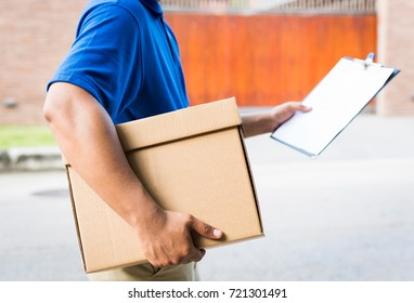 Deliver man in blue uniform and parcel cardboard box