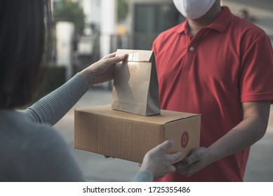 Deliver man wearing face mask in red uniform handling bag and  parcel box give to female costumer Postman and express grocery delivery service during covid19.