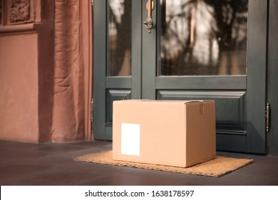 Delivered parcel on door mat near entrance