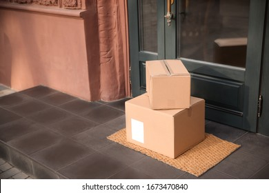 Delivered parcels on door mat near entrance. Space for text