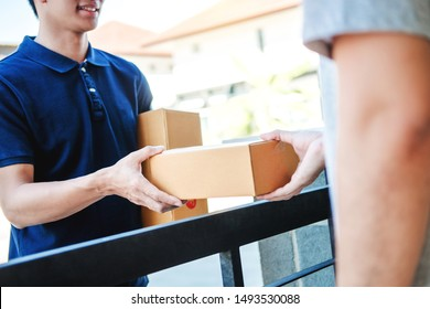 Delivery Asian man service with boxes in hands standing in front of Customer's house doors