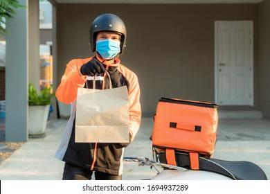 アジア人男性はオレンジの制服を着て、お客の家の前でスクーターにケースボックスと食べ物袋を届け、エクスプレッスで食べ物を届け、オンラインで買い物をする準備ができています。