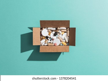 Delivery box filled with assorted prescription medicines and drugs: self medication, addiction and drug abuse concept