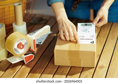 Delivery business. Closeup on woman with packing tape dispenser applying the shipping label to parcel in the office.