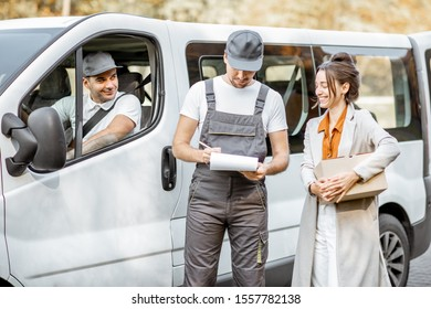 Delivery company employees in uniform delivering goods to a client by cargo van vehicle, woman signing documents and receiving a parcel outdoors