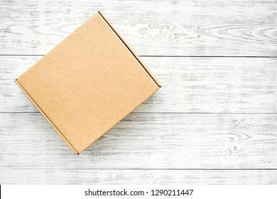 Delivery concept. Cardboard box on white wooden background top view mockup