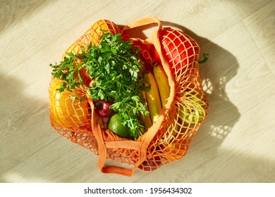 Delivery concept, grocering, Shopping mesh eco bag with healthy vegan vegetables and fruits on the floor at home in sunlight, Healthy eating vegetarian concept.