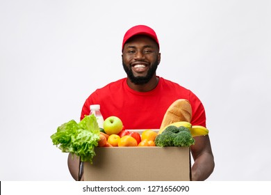 Delivery Concept - Handsome African American delivery man carrying package box of grocery food and drink from store. Isolated on Grey studio Background. Copy Space