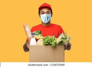 Delivery Concept - Guter afrikanischer Lieferant mit Maske Verpackung von Lebensmitteln und Getränken aus dem Geschäft tragen. Einzeln auf gelbem Studiohintergrund. Leerstelle kopieren.