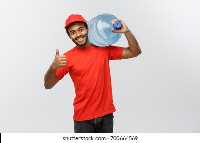 Delivery Concept - Handsome African American delivery man holding water tank. Isolated on Grey studio Background. Copy Space.