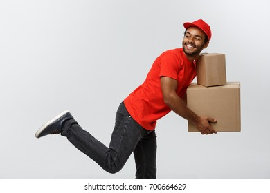 Delivery Concept - Handsome African American delivery man rush running for delivering a package for customer. Isolated on Grey studio Background. Copy Space.